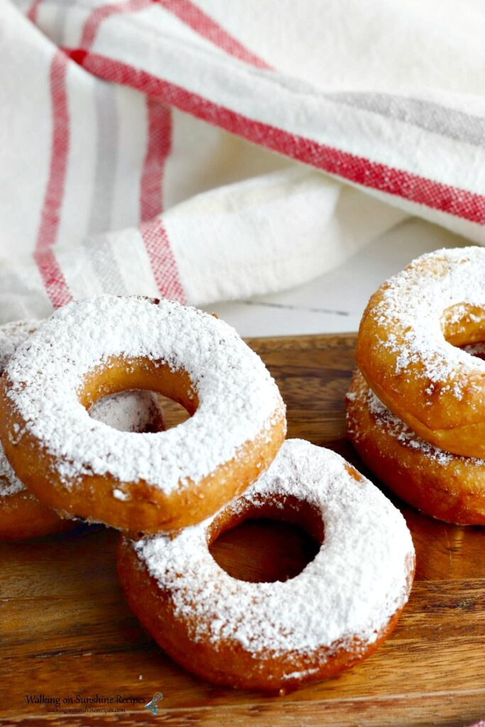Biscuit donuts sprinkled with powdered sugar on cutting board.