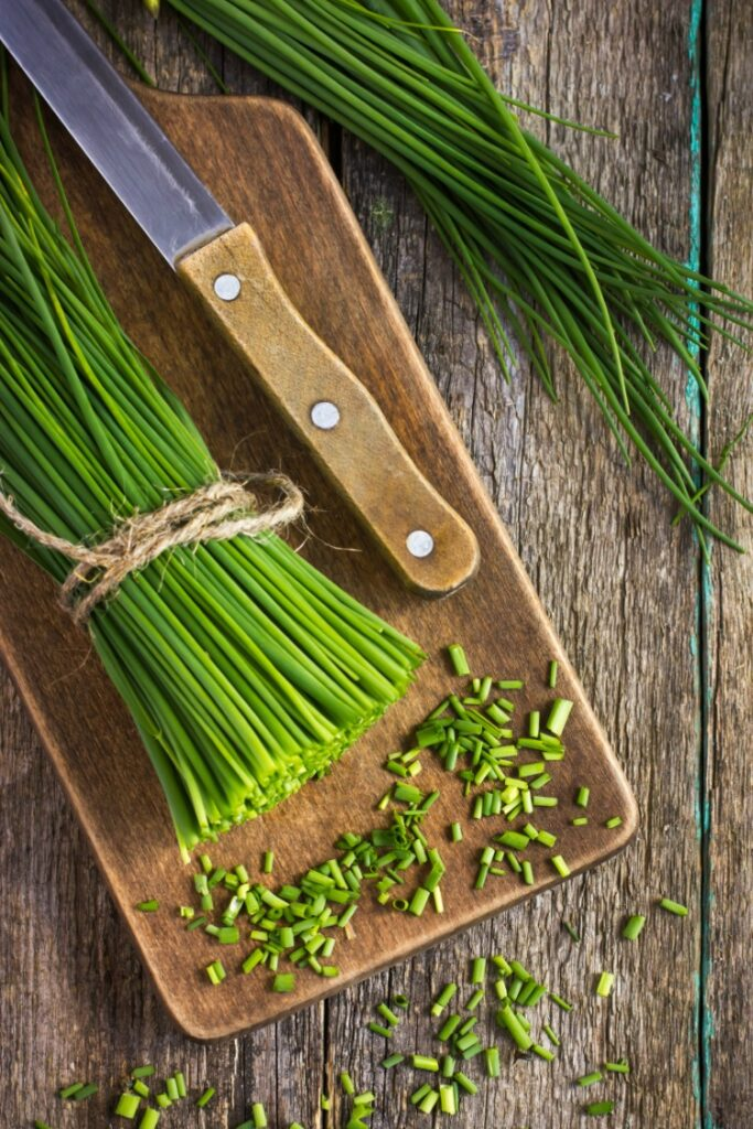 Chopped chives on cutting board with knife.