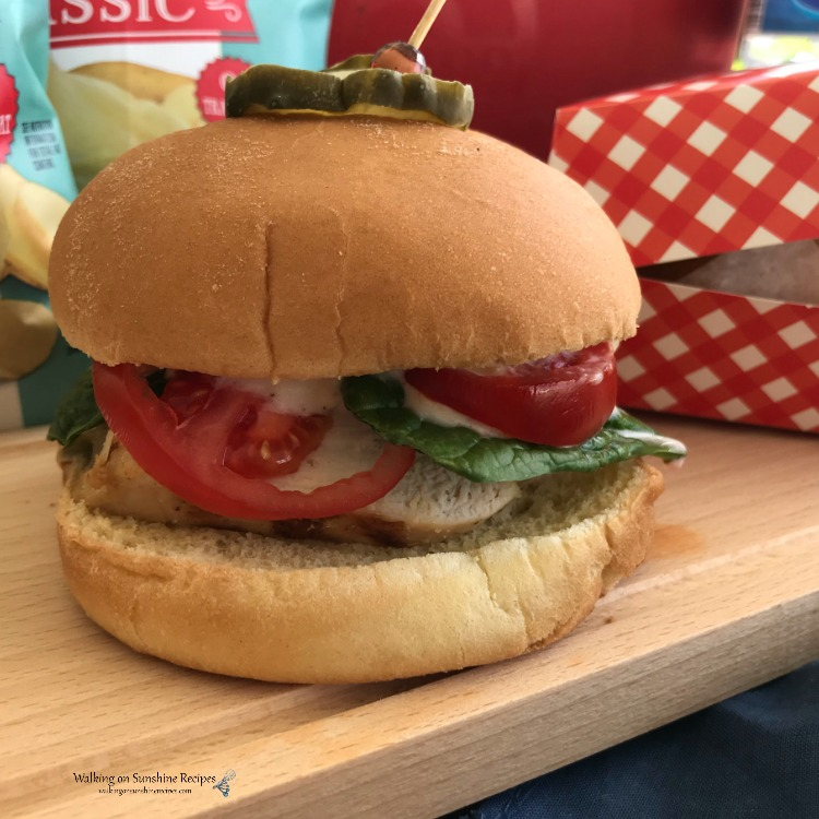 Grilled Chicken Sandwiches with tomato, fresh spinach and a pickle on top.