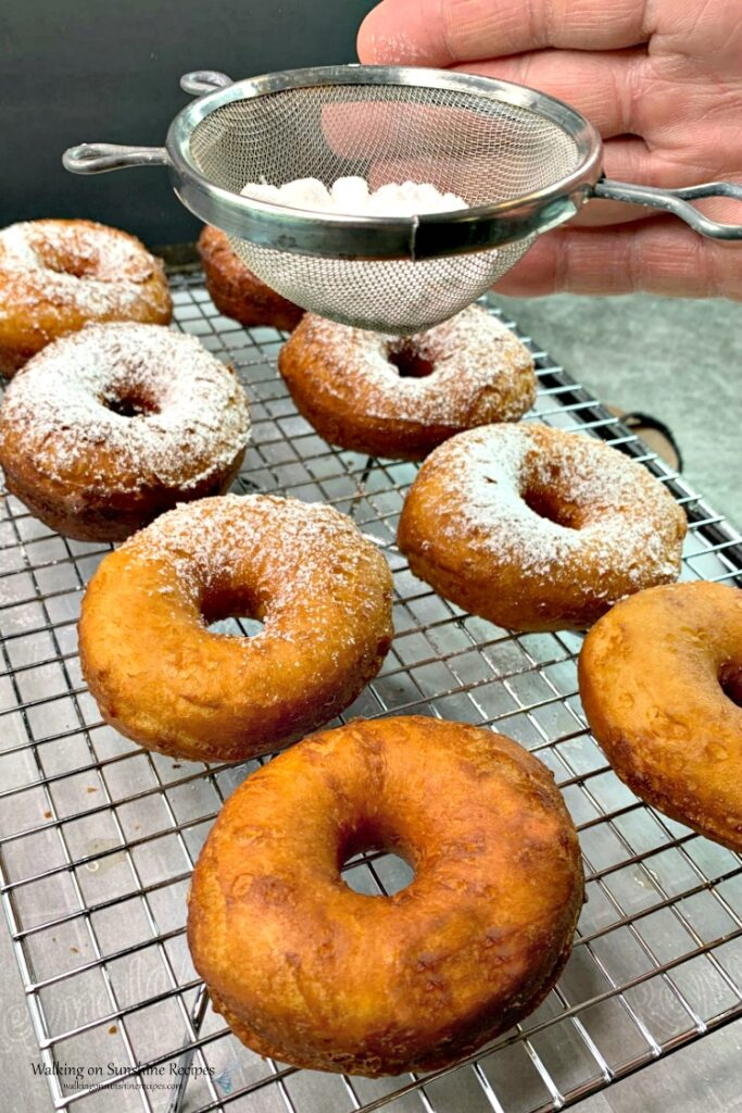 Sprinkle fresh fried biscuit donuts with powdered sugar