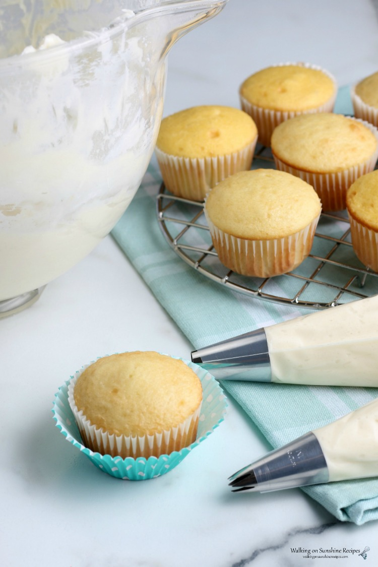 Homemade Cream Cheese Frosting in piping bags and cake mix vanilla cupcakes.