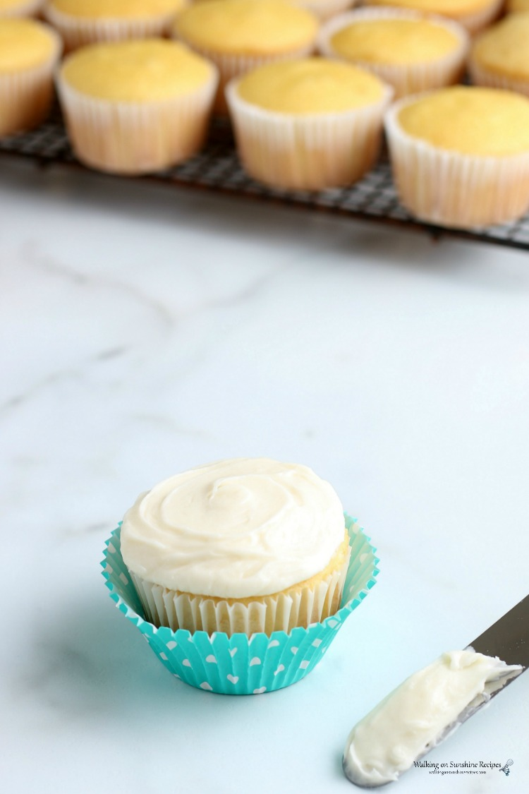 Vanilla cupcake with cream cheese frosting and off-set spatula.