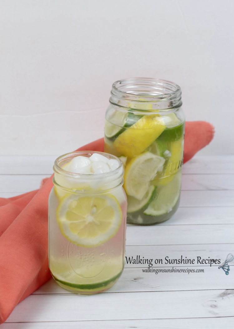 Large and small mason jars containing lemons, limes, water and ice. Displayed besdie an orange cloth napkin.