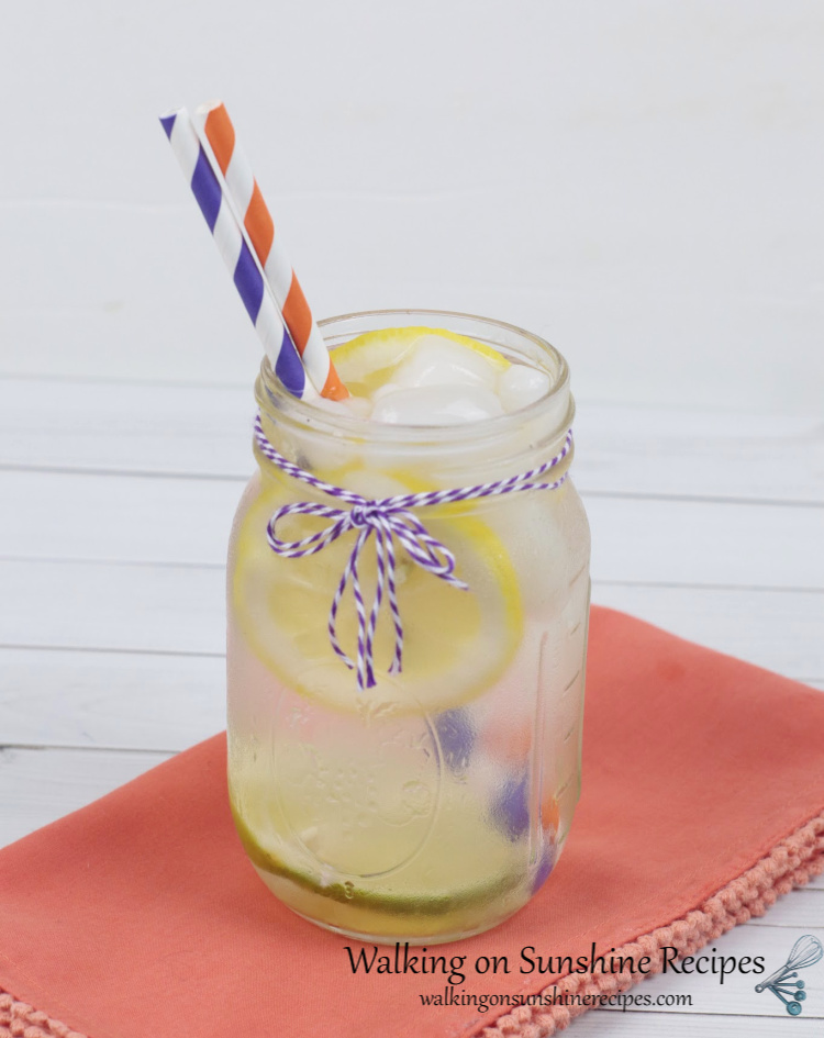 Lemon lime water in a mason jar with purple and orange striped paper straws. Displayed on an orange cloth napkin.