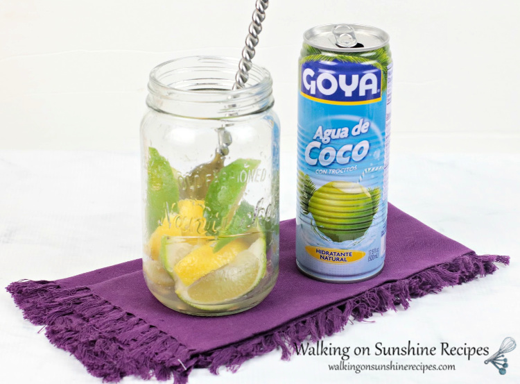 Can of Goya coconut water beside mason jar with lemon and lime slices inside. Large spoon is inside jar, too. All displayed on a purple cloth napkin.