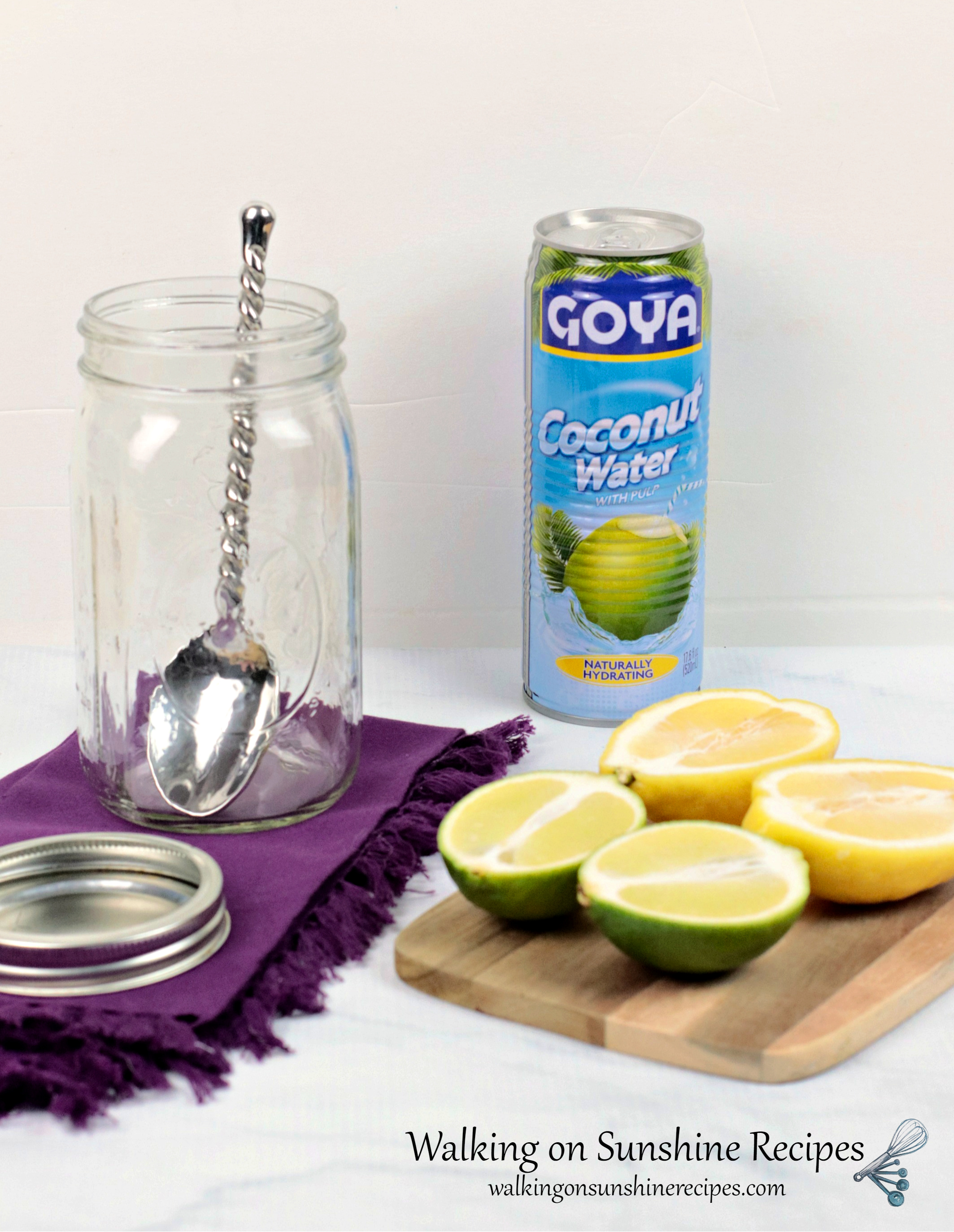Lemon lime water ingredients and tools. Can of Goya coconut water, lemon cut in half, lime cut in half displayed on wood cutting board. Empty mason jar with large metal spoon inside on top of a purple cloth napkin.