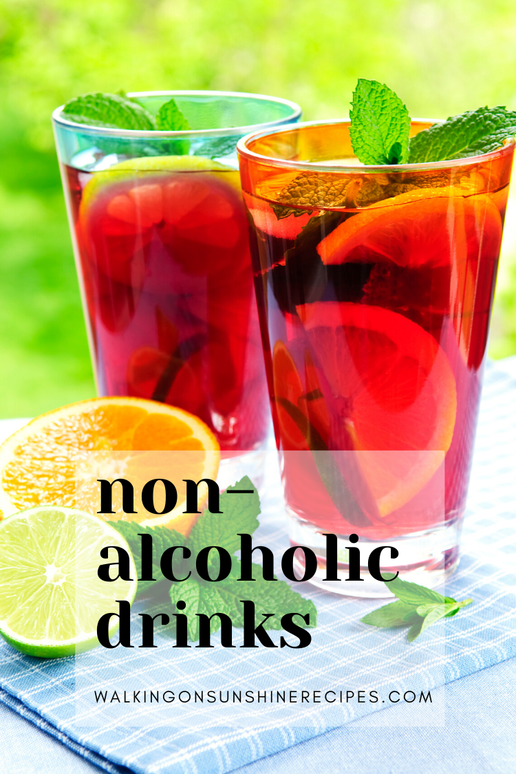 two glasses of strawberry lemonade with fresh lemons and fresh mint.
