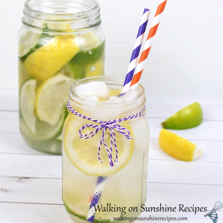 Background shows mason jar filled with lemons and limes and water. Foreground shows small mason jar with filled with lemon lime water with purple striped and orange stripes paper straws. Also accented with a purple and white string bow around neck of jar.