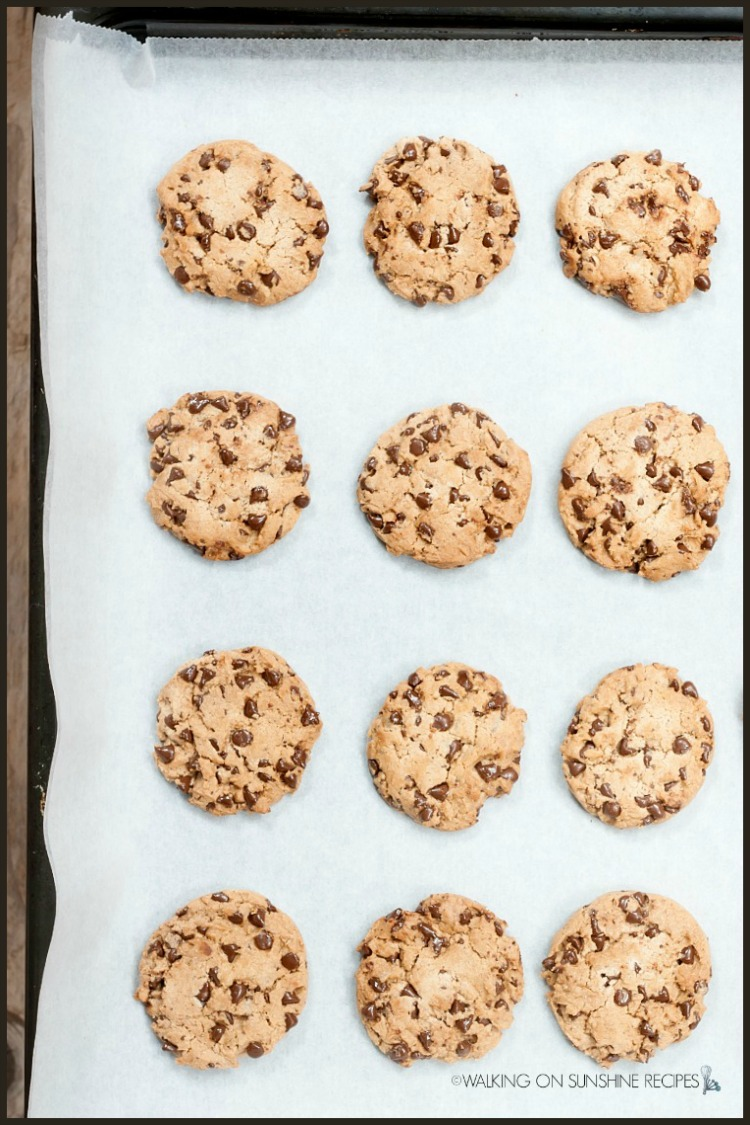 12 chocolate chip cookies baked on baking tray lined with parchment paper.