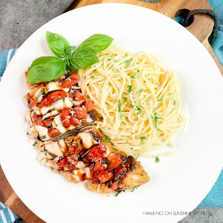 30 Minute Caprese Chicken on white plate with spaghetti.