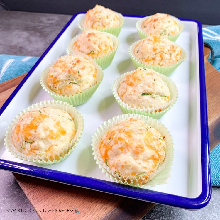 Featured photo Bisquick Zucchini Cheddar Muffins on white and blue tray