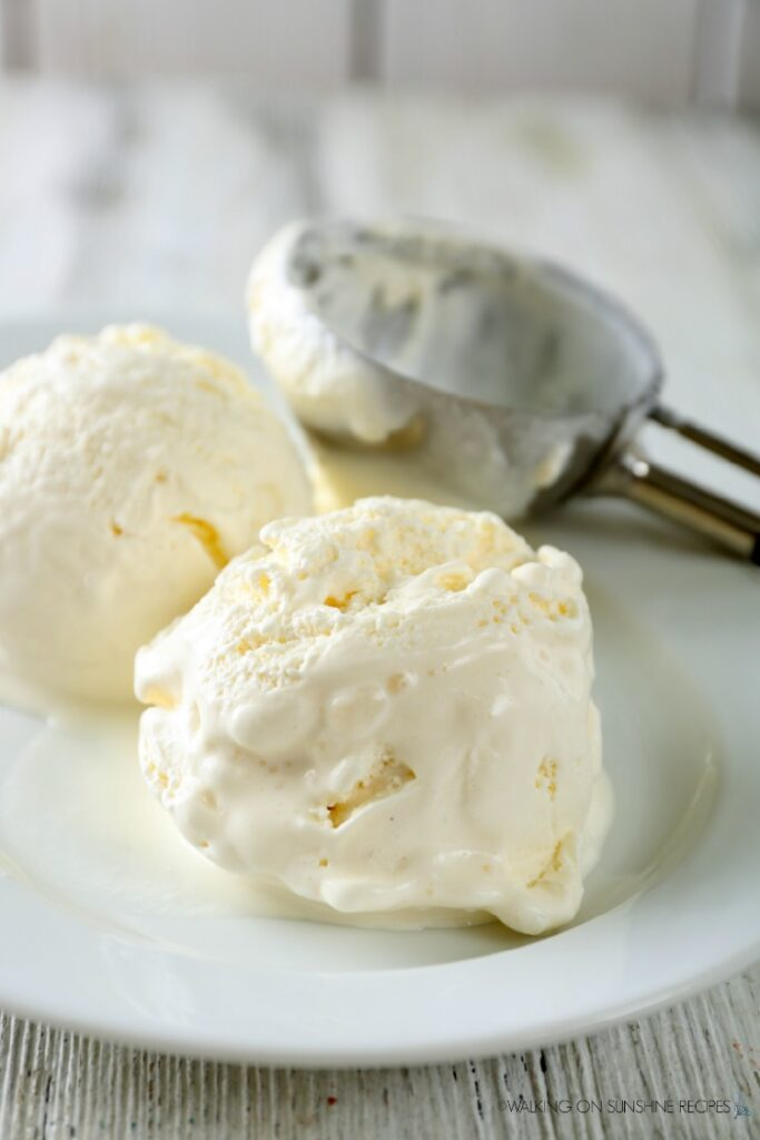 Scoops of homemade ice cream on white plate with ice cream scoop.