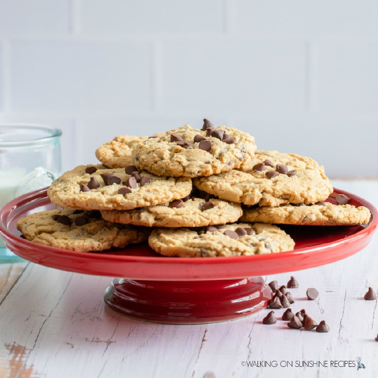 Stacked chocolate chip cookies on red cake plate with glass of milk in the background.