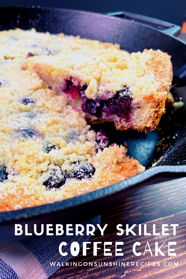 sliced piece of blueberry crumb cake in cast iron skillet.