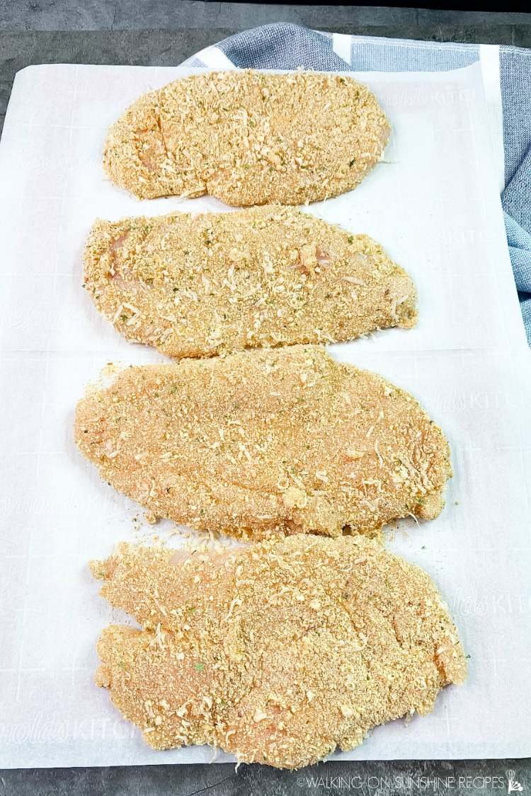 Breaded Chicken Cutlets on cutting board ready to cook