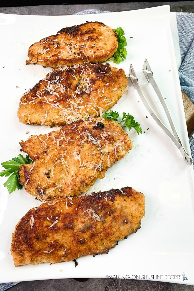 Four boneless skinless chicken breasts cooked on white platter.