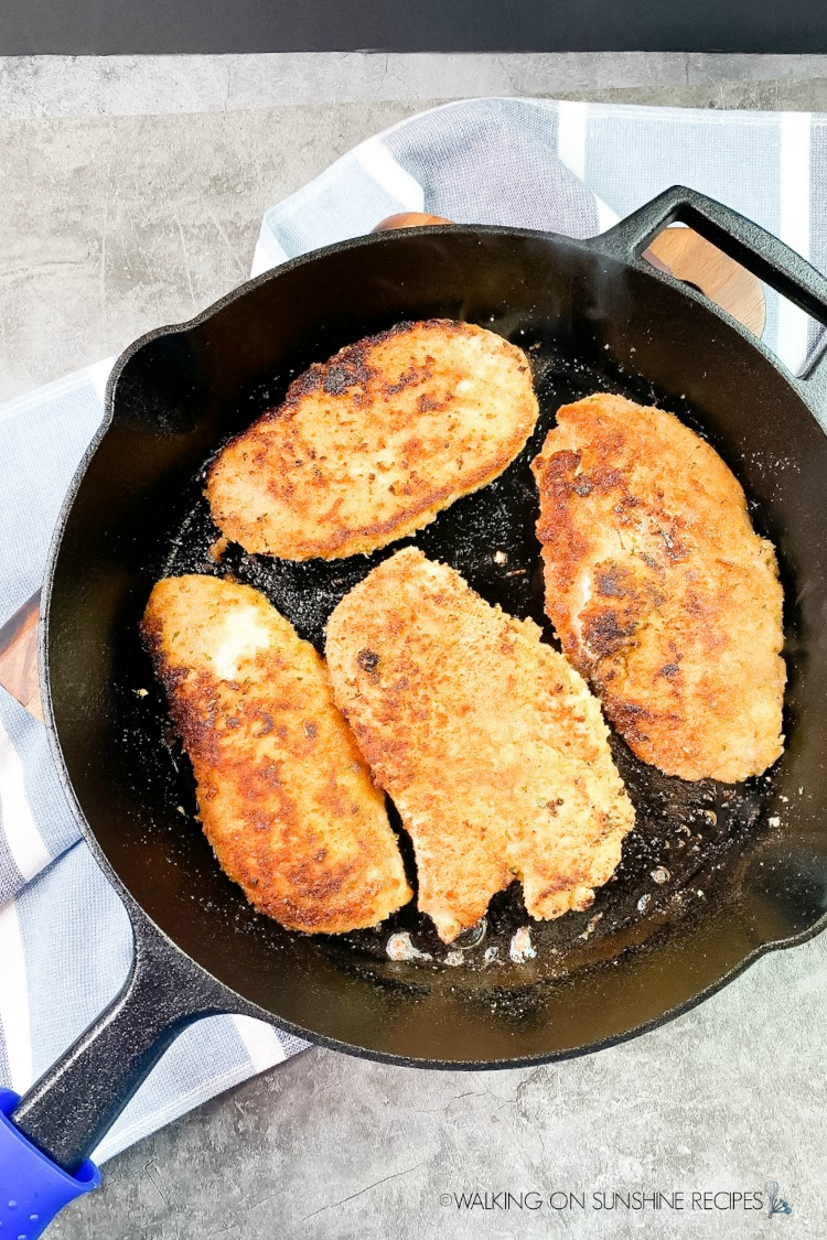 cooked chicken cutlets in cast iron skillet pan.