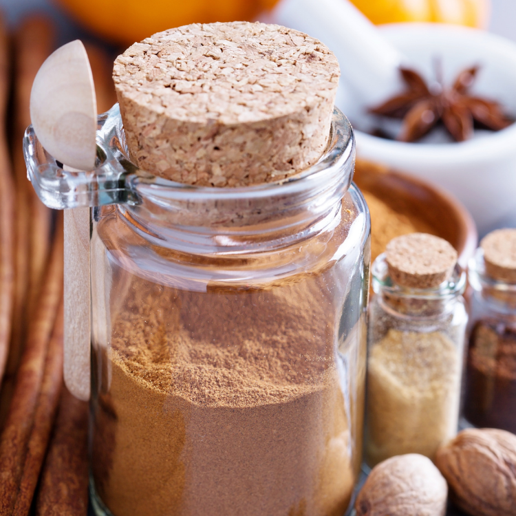 spice jar with spoon filled with homemade pumpkin pie spice.