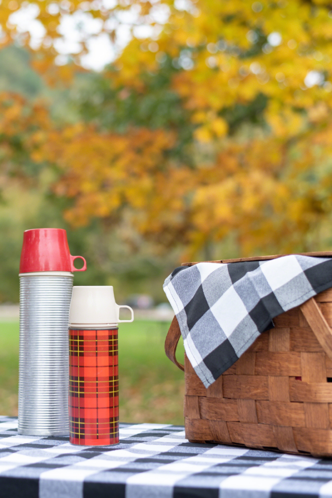 Fall picnic table with basket and two thermos'