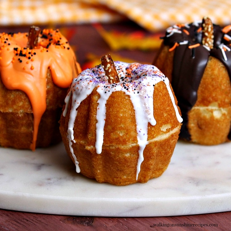 Mini pumpkin bundt cakes with vanilla, chocolate and orange frosting.
