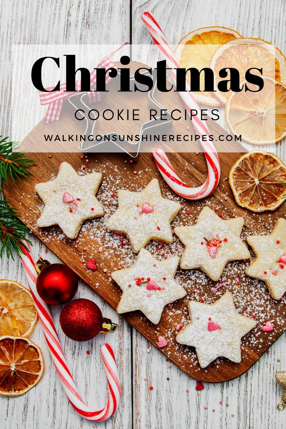 Christmas cookies in the shape of stars with peppermint candy canes and orange slices on cutting board.