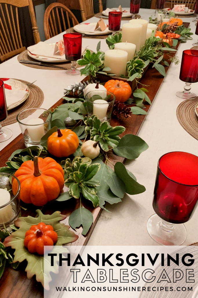 dining room table set with dishes, glasses, candles, pumpkins and greenery.