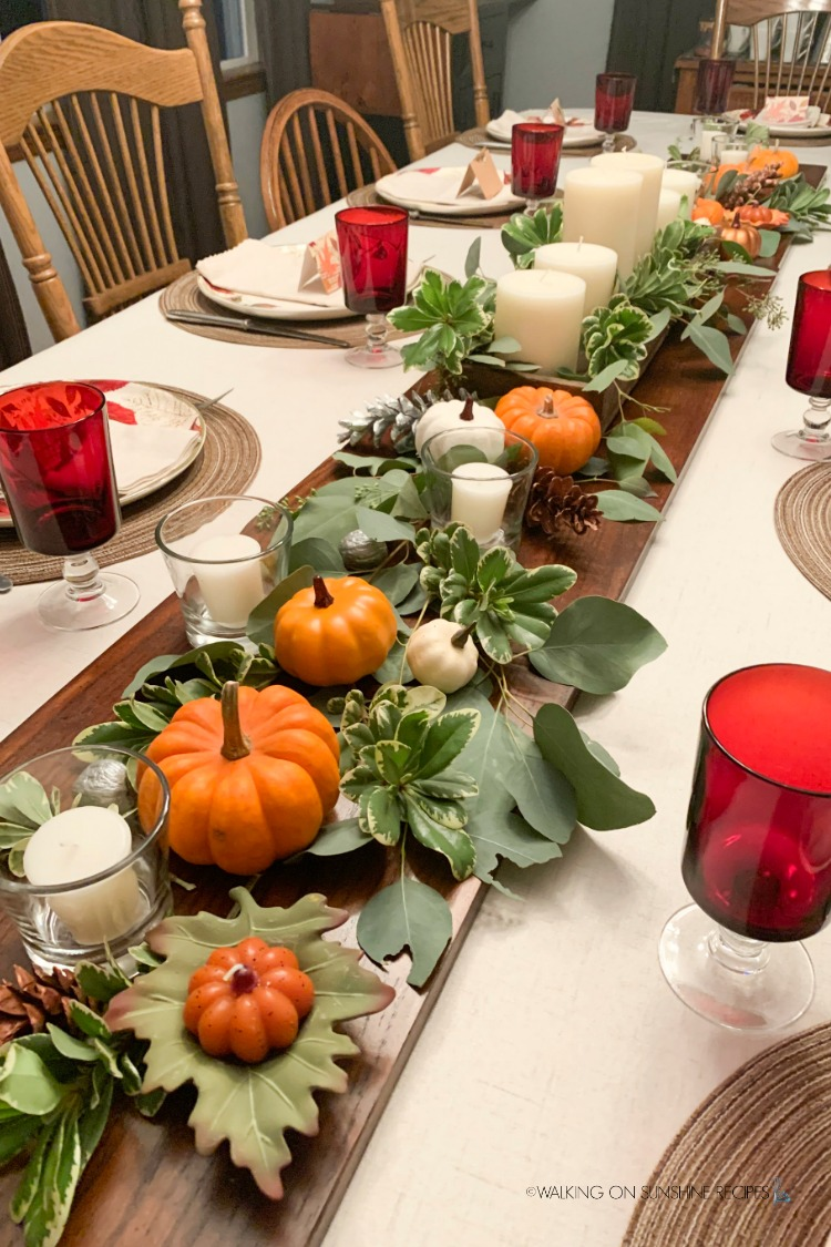 Thanksgiving table set with pumpkins, candles and greenery.