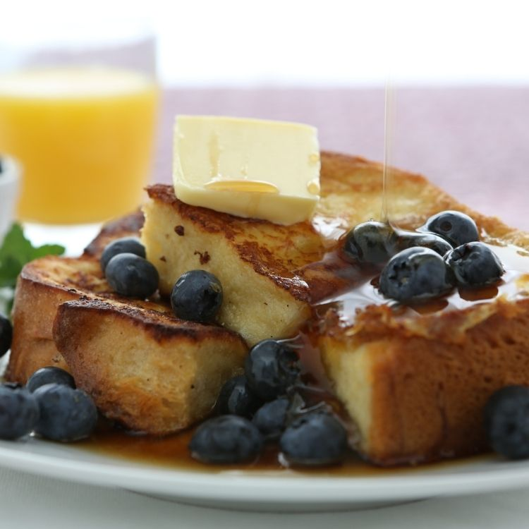 French toast bake with Texas toast served with butter, syrup and fresh blueberries.