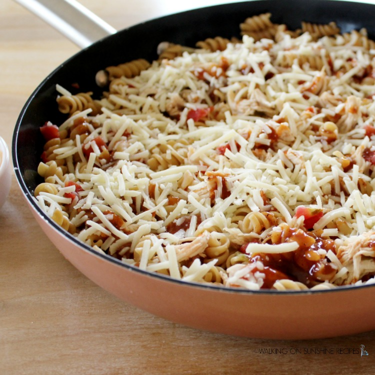 Add cheese on top of pasta and chicken.