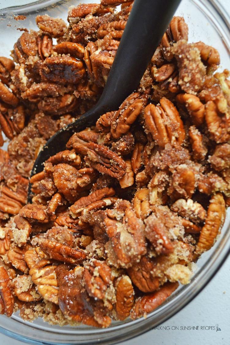 Combine sugar, cinnamon with pecans in bowl