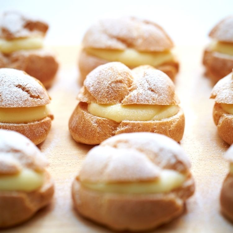 homemade cream puffs filled with pudding on platter.