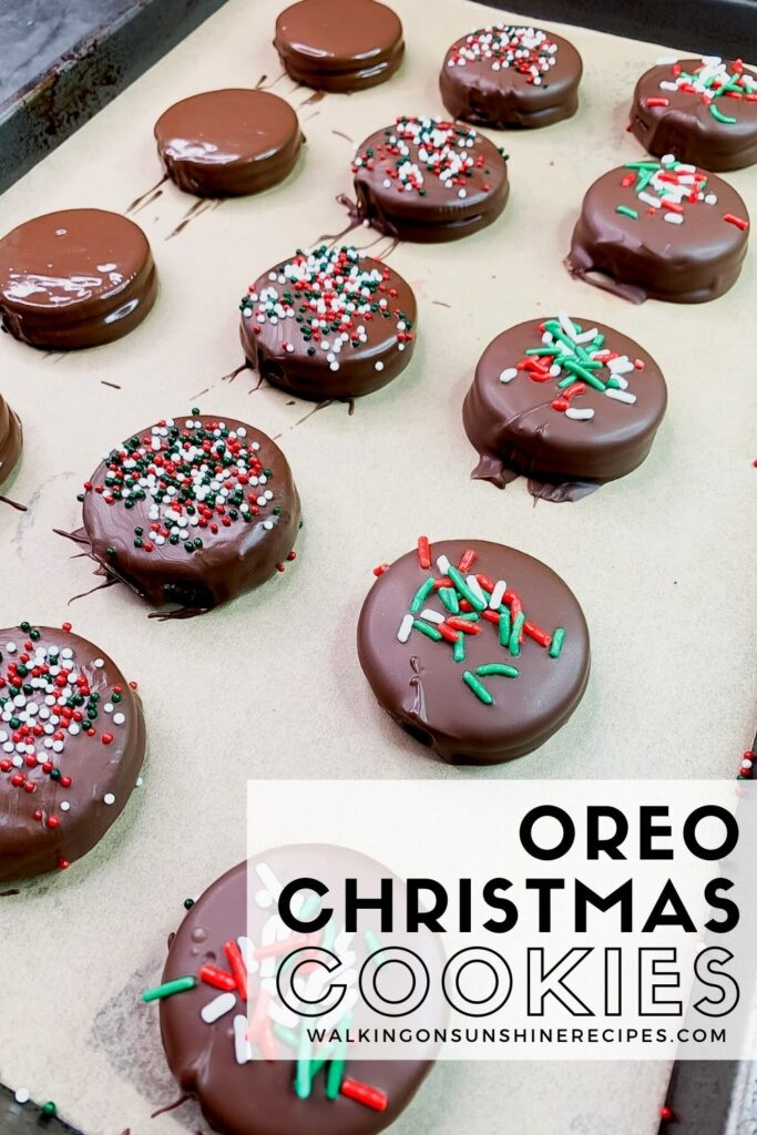 chocolate covered sandwich cookies with Christmas sprinkles on baking tray lined with parchment paper.