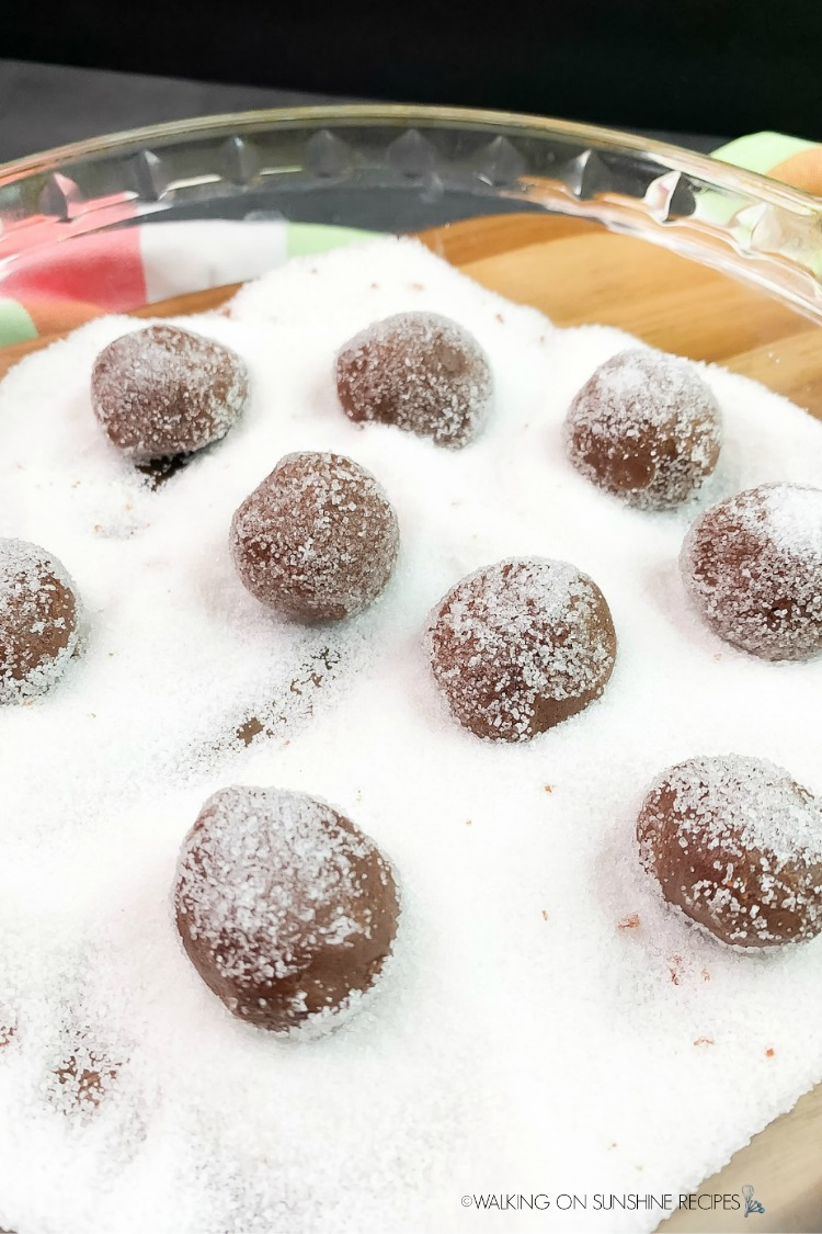 Roll cookie balls in white sugar before placing on baking tray to bake