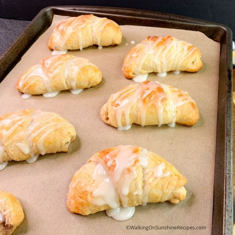Crescent rolls stuffed with cream cheese sugar mixture on baking tray.