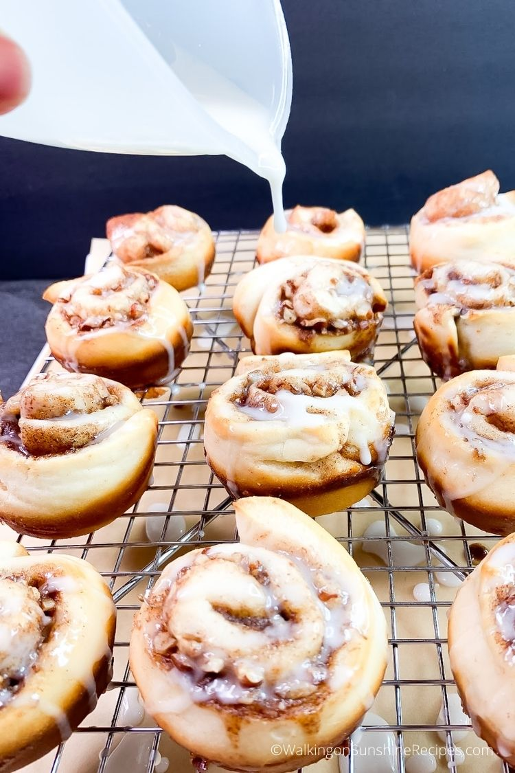 glaze being poured on top of cinnamon rolls with refrigerator biscuits.