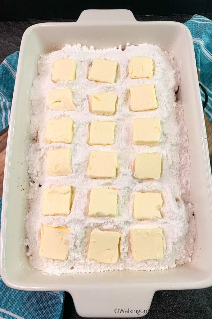 dump cake with white cake mix and butter slices.