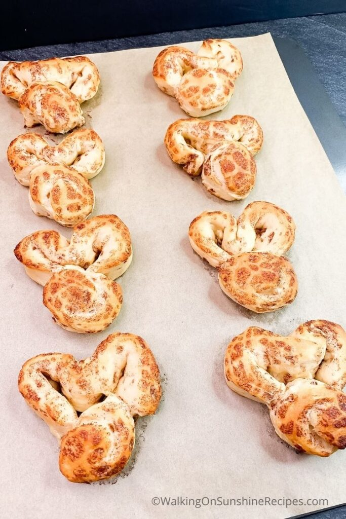 baked bunny cinnamon rolls on parchment paper lined tray.