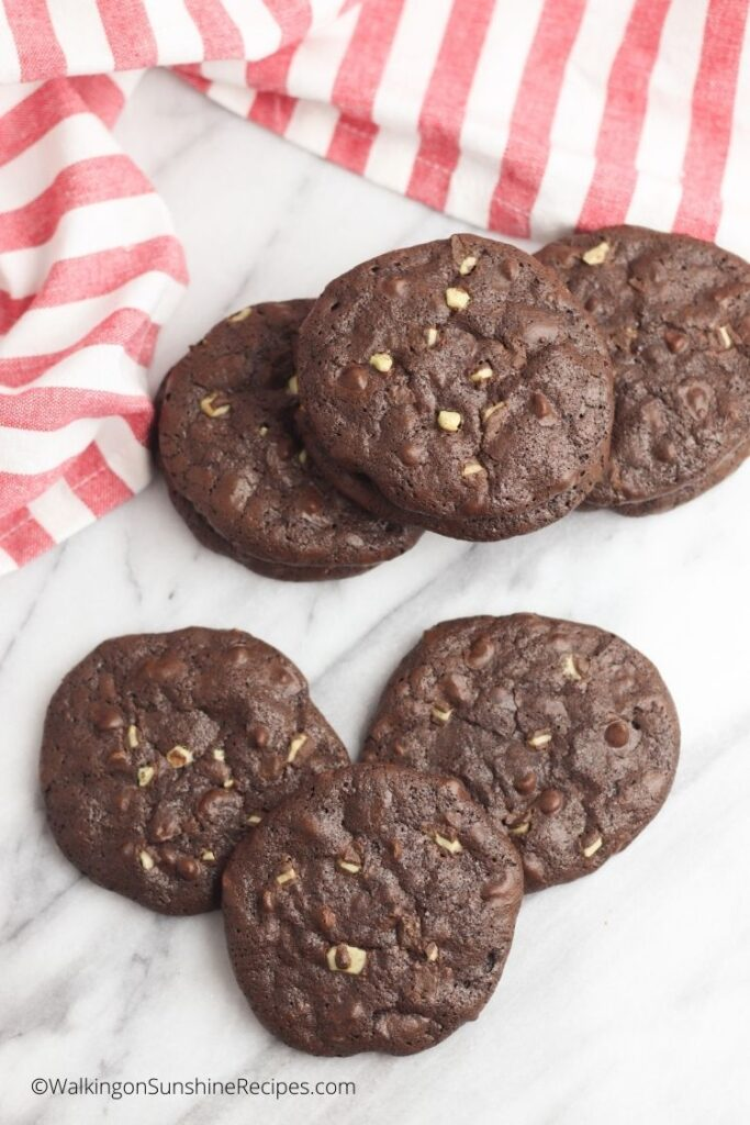 Brownie mint chip cookies on white board with red and white napkin.