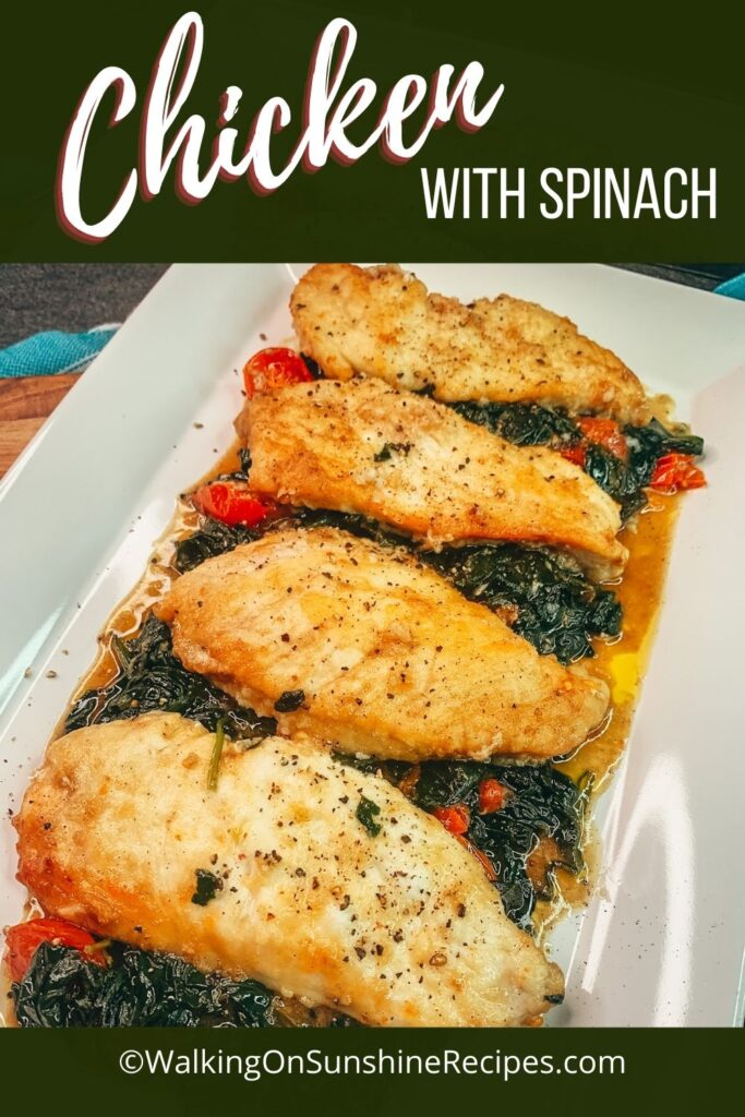Chicken with spinach and tomatoes on white platter.