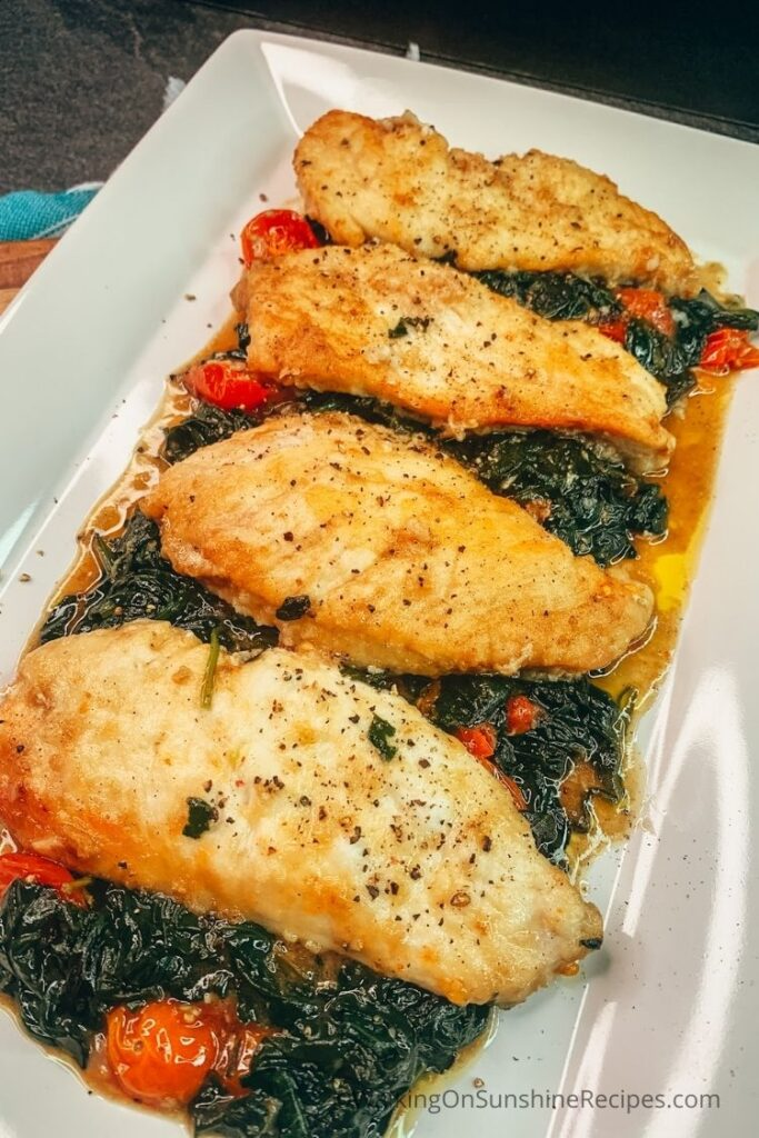 Chicken cooked with spinach and tomatoes on white platter.