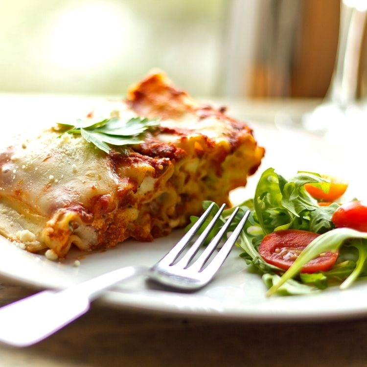 Lasagna on white plate with salad.