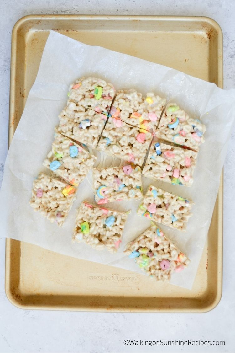 Marshmallow cereal bars on parchment paper in baking tray.