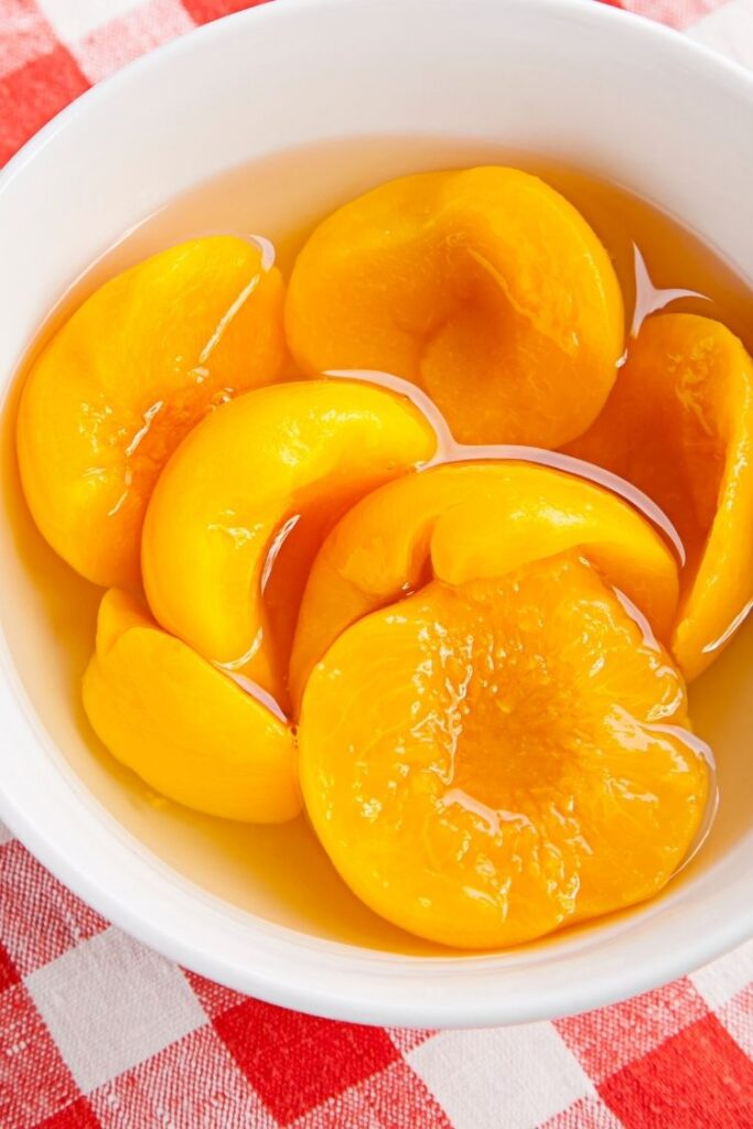 peaches in white bowl with juice.