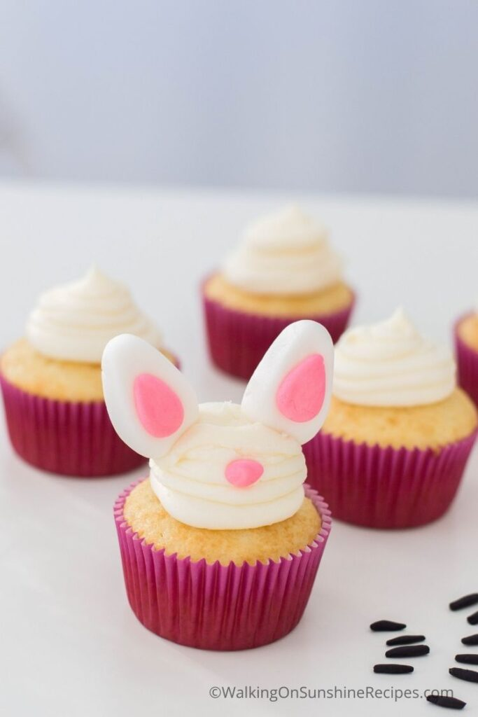 Add the fondant bunny ears to the vanilla cake mix cupcakes.