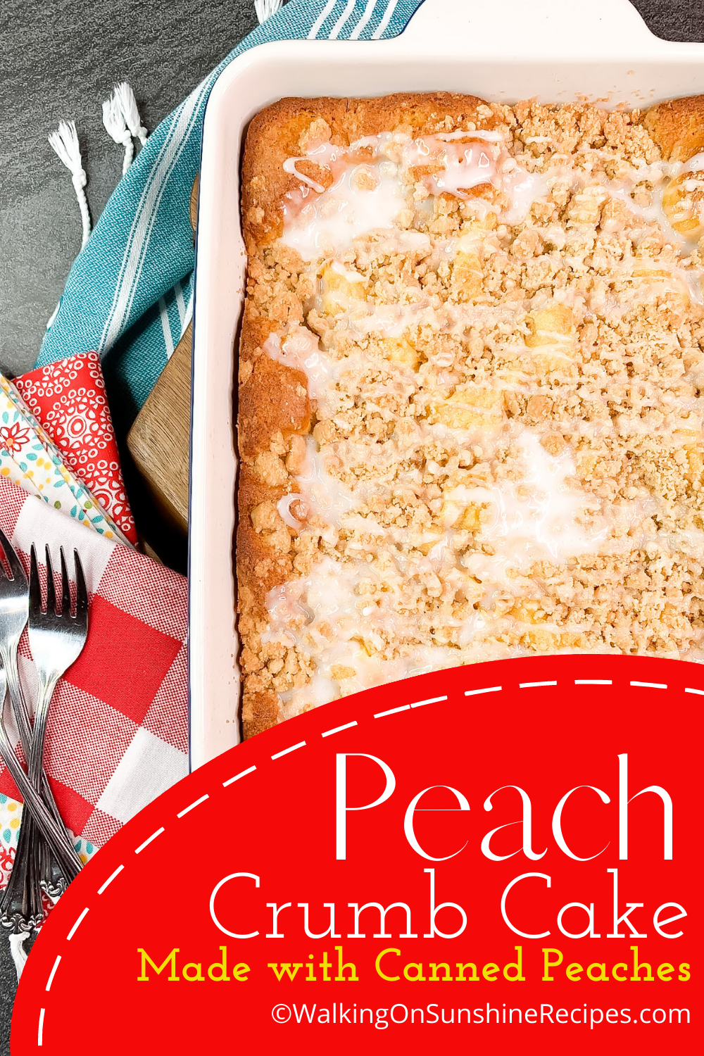 baked peach crumb cake with powdered sugar glaze in white baking dish.