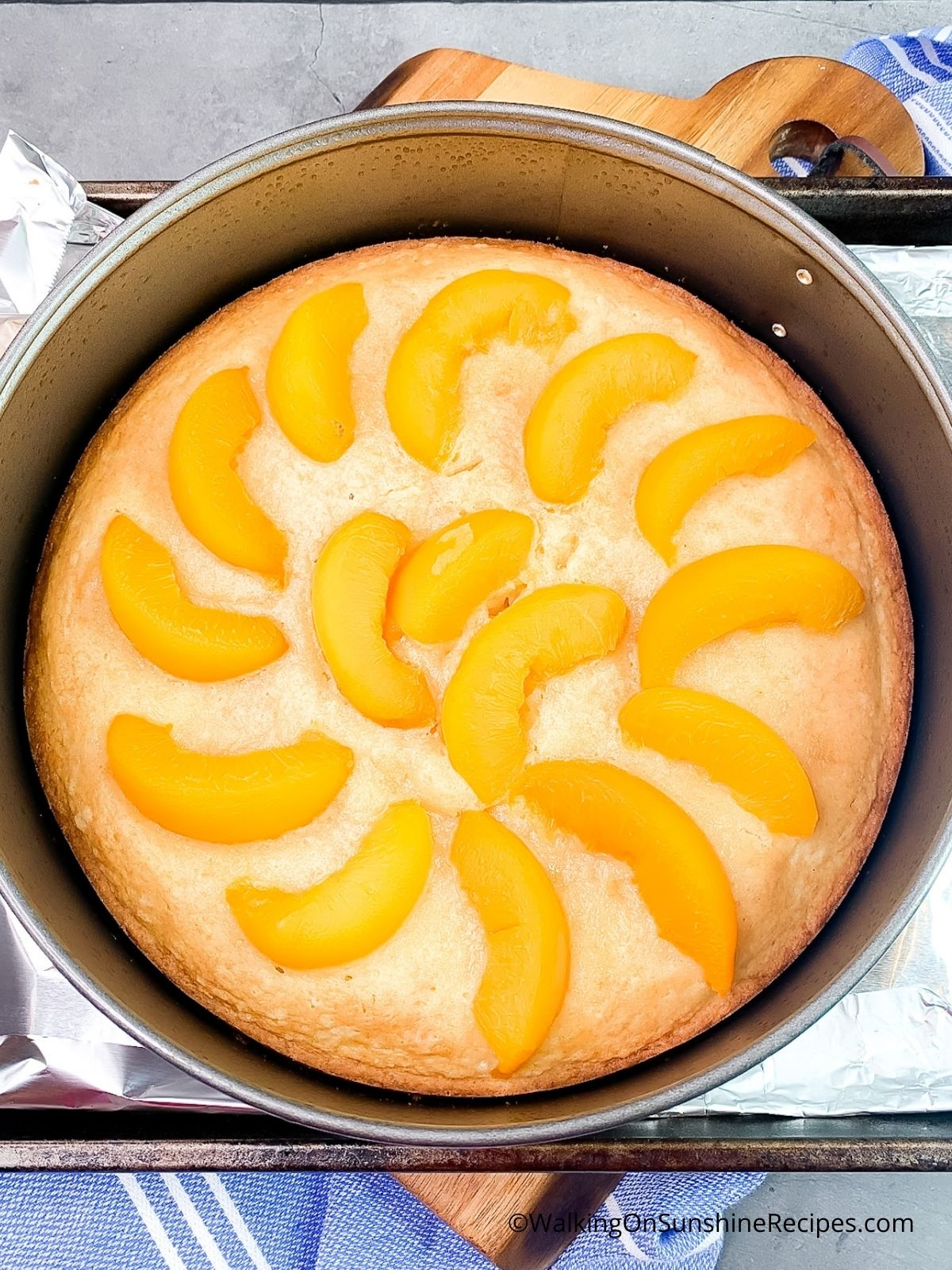 Add canned peaches to partially baked peach cake