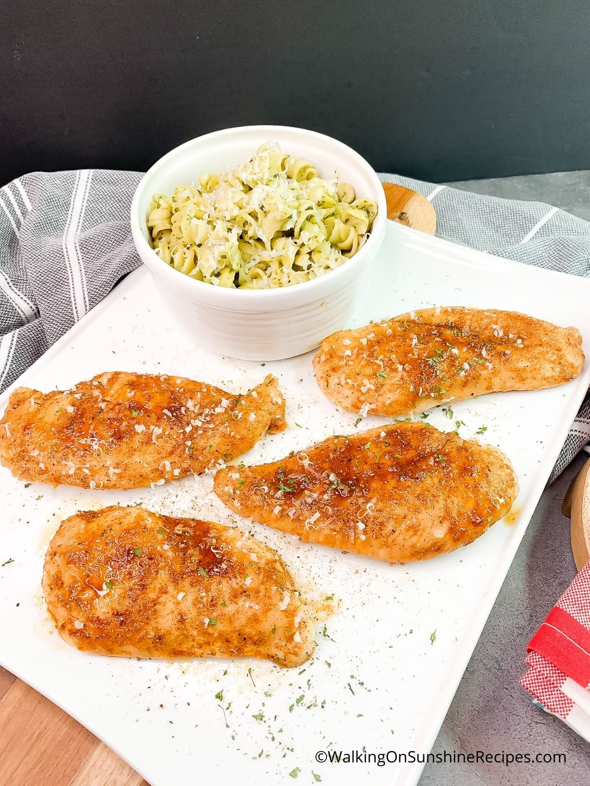 Baked Moist Chicken Cutlets on white platter with pasta in small bowl.