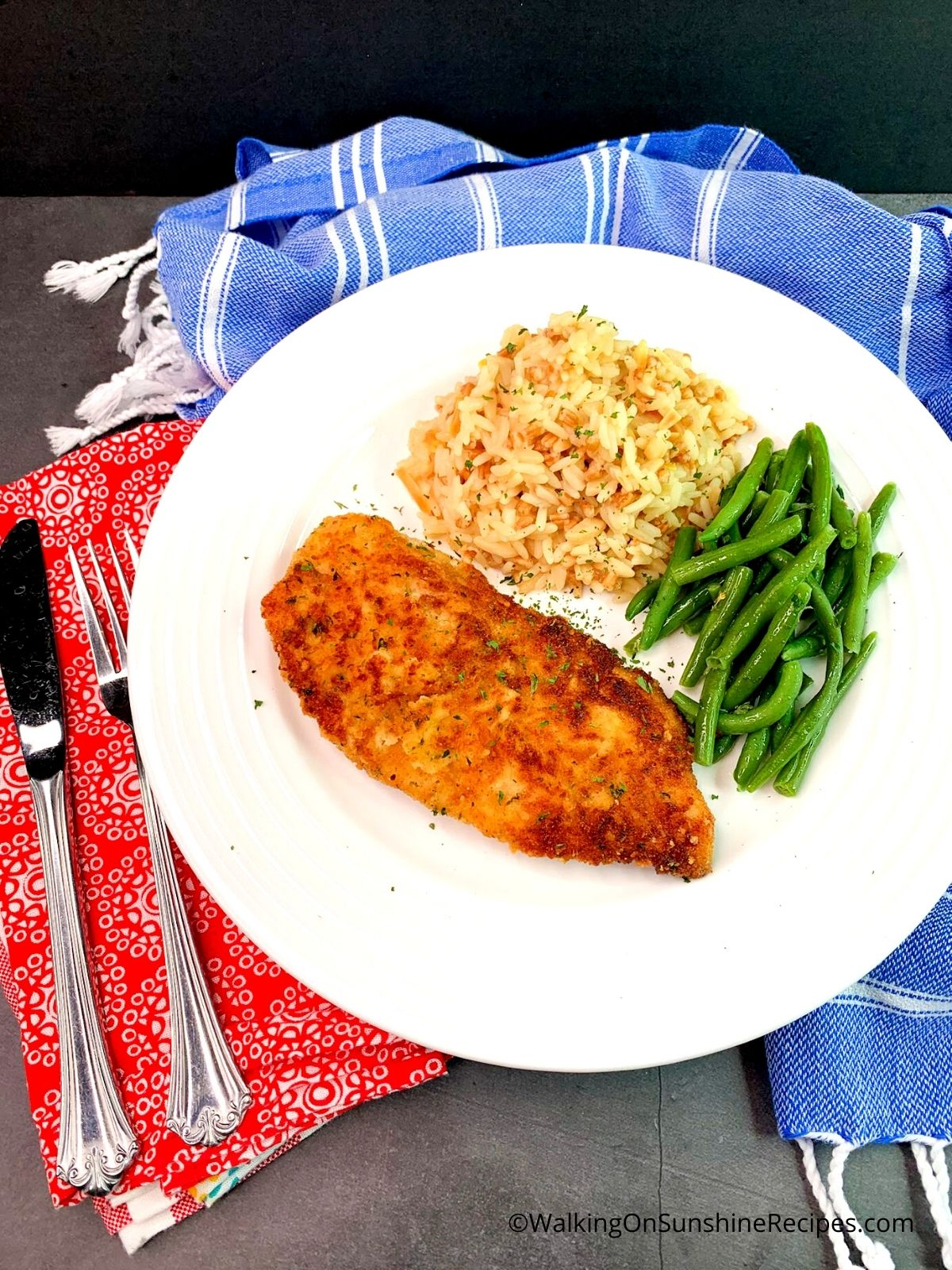 Breaded Chicken Cutlets on white plate with rice pilaf and steamed green beans.