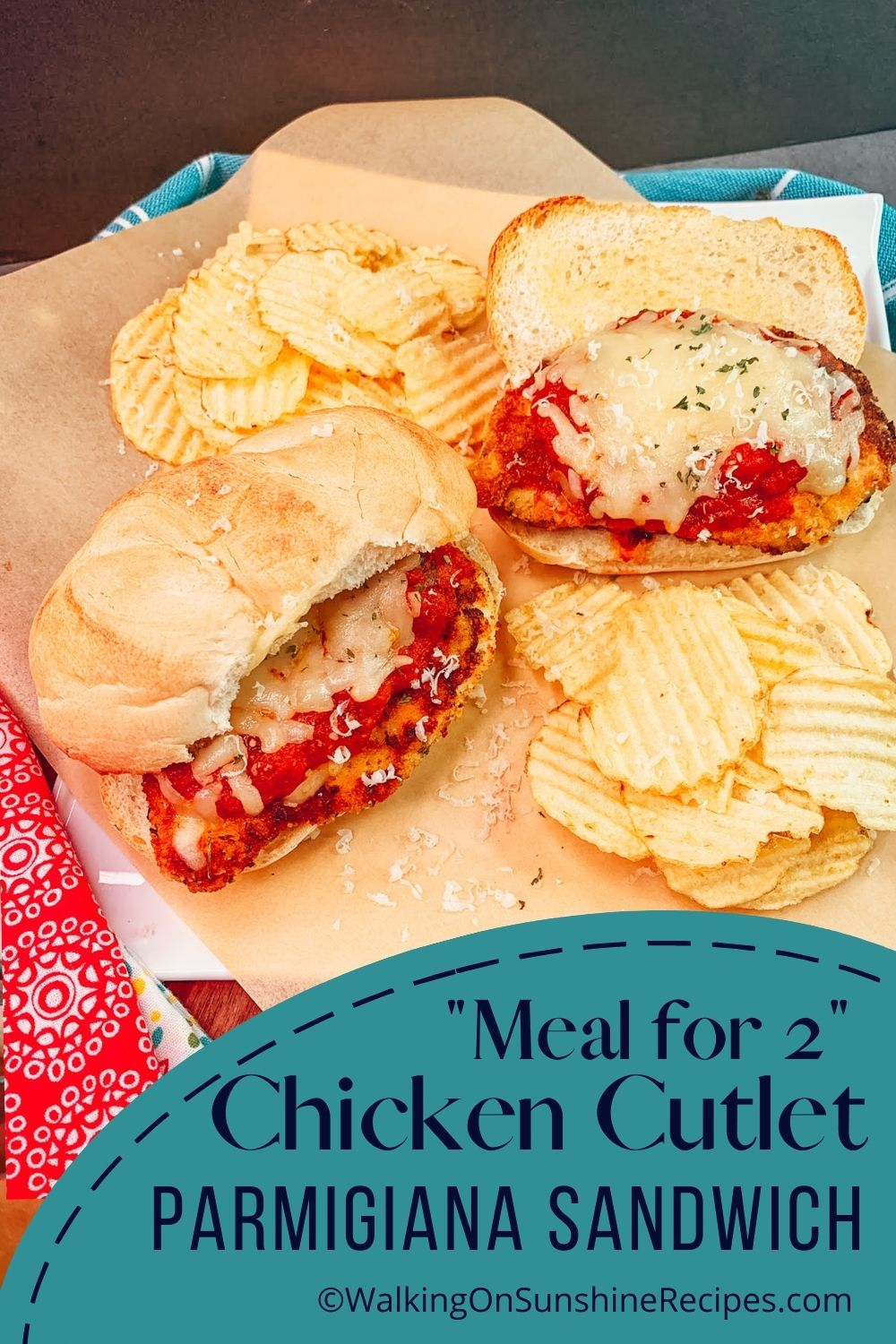 two chicken Parmigiana sandwiches on platter with potato chips.
