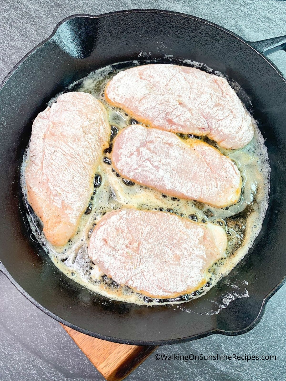 Chicken cutlets cooking in cast iron skillet pan.